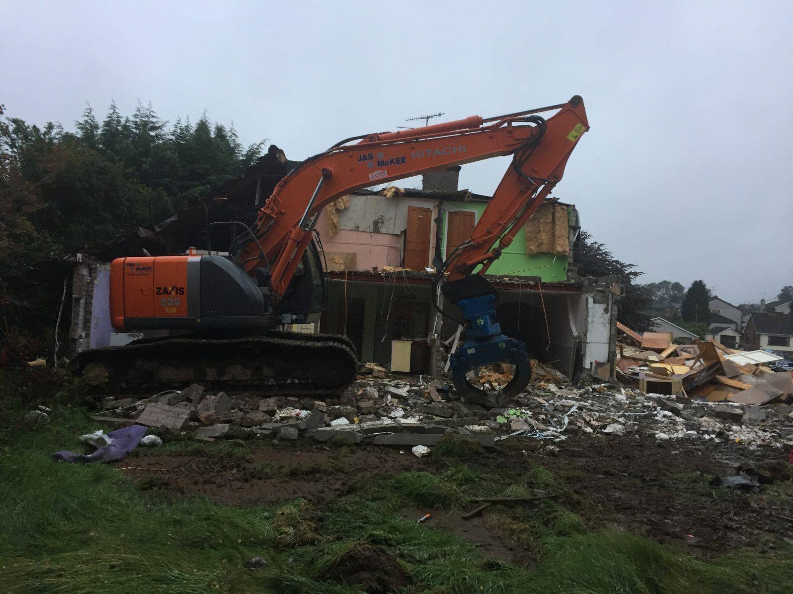 Demoliting existing buildings using grab on Excavator