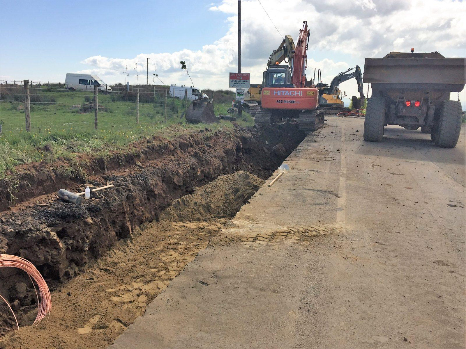 Digging trench for powerline on road to windfarm